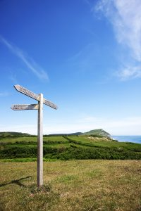 A signpost on the Jurassic Coast, Dorset, UK. Golden cap in the background.
